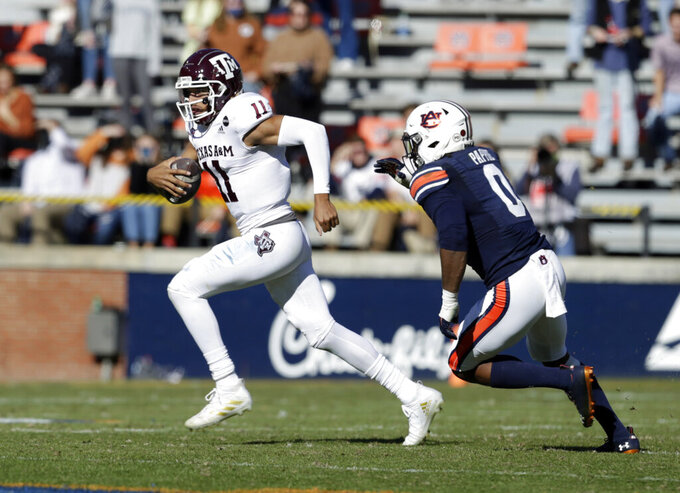 Texas A&M quarterback Kellen Mond (11) scrambles away from pressure from Auburn linebacker Owen Pappoe (0) during the second half of an NCAA college football game on Saturday, Dec. 5, 2020, in Auburn, Ala. (AP Photo/Butch Dill)