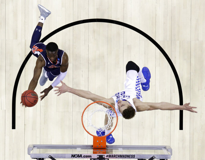 Auburn's Jared Harper, left, drives to the basket past Kentucky's Reid Travis during the first half of the Midwest Regional final game in the NCAA men's college basketball tournament Sunday, March 31, 2019, in Kansas City, Mo. (AP Photo/Charlie Riedel)
