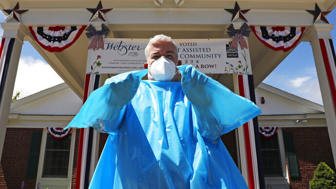 Brendan Williams, president of the New Hampshire Health Care Association, wears an isolation gown with no sleeve openings for hands, which was received in a shipment from the federal government, outside Webster at Rye senior care center on Wednesday, July 1, 2020, in Rye, N.H. The problematic gowns, child-sized examination gloves and surgical masks with ear loops that break when stretched make up the bulk of the personal protective equipment recently sent by the Federal Emergency Management Agency to New Hampshire nursing homes, according to Williams. The facility is not using the items they received from FEMA. (AP Photo/Charles Krupa)