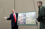 FILE - In this March 13, 2018, file photo, President Donald Trump holds a poster with photographs of the U.S. - Mexico border area as he reviews border wall prototypes in San Diego with Rodney Scott, the U.S. Border Patrol's San Diego sector chief. U.S. District Judge Haywood Gilliam Jr. has blocked President Donald Trump from building sections of his long-sought border wall with money secured under his declaration of a national emergency, Friday, May 24, 2019. (AP Photo/Evan Vucci, File)