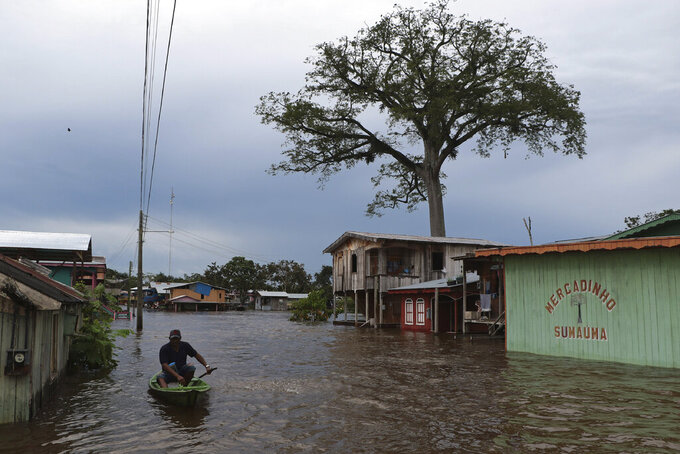 A resident navigates a flooded street in Anama, Amazonas state, Brazil, Thursday, May 13, 2021. (AP Photo/Edmar Barros)