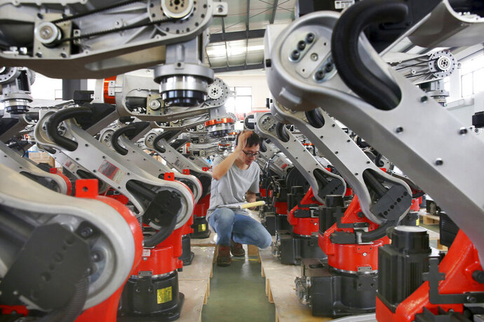 In this Wednesday, Sept. 11, 2019, photo, a man checks on the robotic arms at a factory making industrial robots in Zhengyu town of Haimen city in east China's Jiangsu province. A Chinese envoy is going to Washington on Wednesday, Sept. 18, to prepare for trade negotiations. The announcement Tuesday, Sept. 17, follows conciliatory gestures by both sides ahead of the October talks on their fight over trade and technology, which threatens to dampen global economic growth. (Chinatopix via AP)