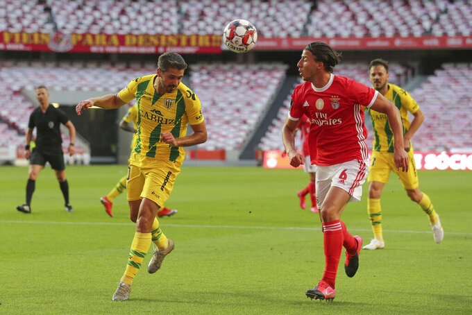 Benfica's player Ruben, right, vies for the ball with Tondela's Filipe Ferreira during a Portuguese League soccer match between Benfica and Tondela in Lisbon, Portugal, Thursday, June 4, 2020. The Portuguese League soccer matches resumed Wednesday without spectators because of the coronavirus pandemic. (Tiago Petinga/Pool via AP)