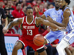 North Carolina State's C.J. Bryce (13) loses the ball while being defended by North Carolina's Leaky Black (1) during the first half of an NCAA college basketball game at PNC Arena in Raleigh, N.C., Monday, Jan. 27, 2020. (Ethan Hyman/The News & Observer via AP)