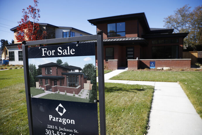 FILE - In this Oct. 22, 2019, photo a sign stands outside a new home for sale in southeast Denver.  U.S. long-term mortgage rates were stable to slightly lower this week after two weeks of declines amid deepening anxiety over the severe damage to the economy from the coronavirus pandemic. Home-loan rates have been hitting all-time lows, and mortgage buyer Freddie Mac says, Thursday, April 9, 2020,  there's room for them to move lower.(AP Photo/David Zalubowski, File)