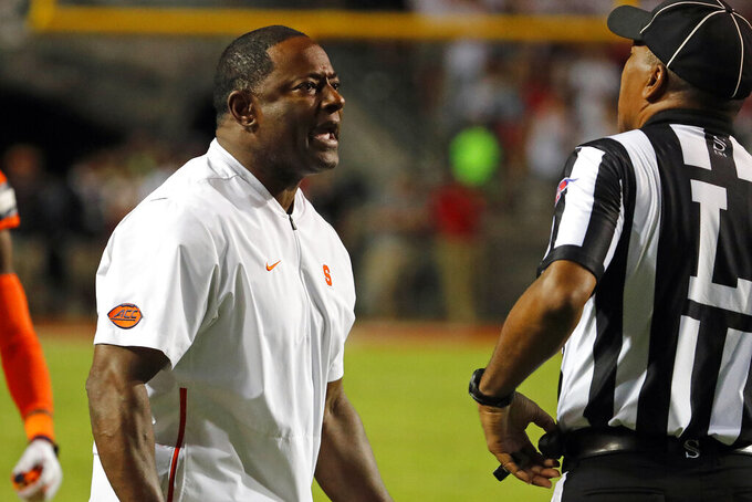 Syracuse coach Dino Babers protests a call with an official during the first half of the team's NCAA college football game against North Carolina State in Raleigh, N.C., Thursday, Oct. 10, 2019. (AP Photo/Karl B DeBlaker)