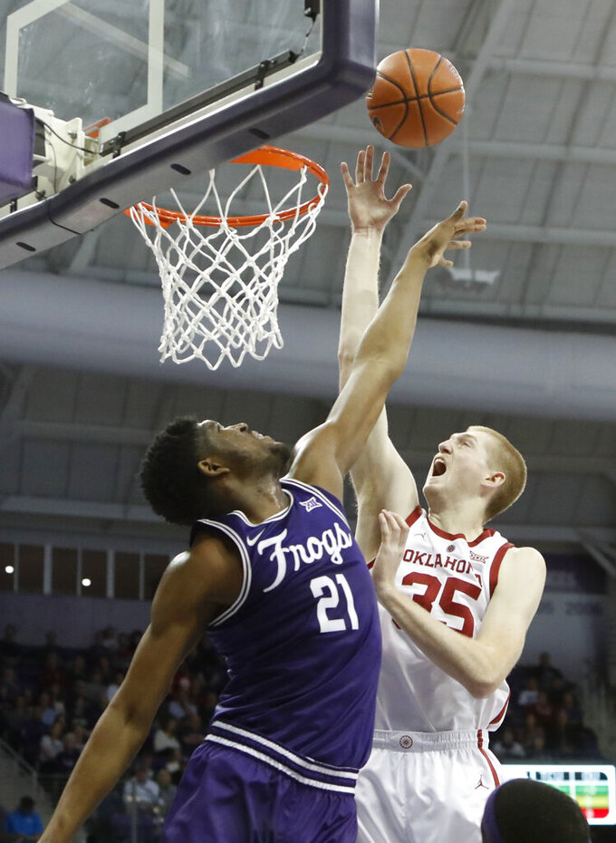 Oklahoma forward Brady Manek (35) shoots against TCU center Kevin Samuel (21) during the first half of an NCAA college basketball game in Fort Worth, Texas, Saturday, Feb. 16, 2019. (AP Photo/LM Otero)