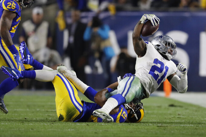 Dallas Cowboys running back Ezekiel Elliott is tackled by Los Angeles Rams cornerback Aqib Talib during the first half in an NFL divisional football playoff game Saturday, Jan. 12, 2019, in Los Angeles. (AP Photo/Marcio Jose Sanchez)