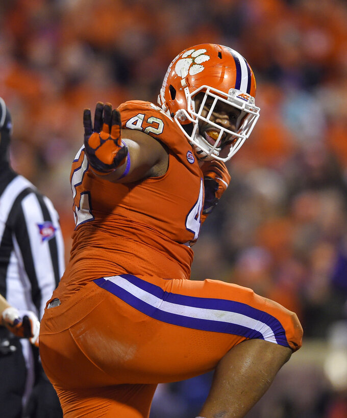 File-This Nov. 24, 2018, file photo shows Clemson's Christian Wilkins doing the Heisman pose after scoring a touchdown during the first half of an NCAA college football game against South Carolina, in Clemson, S.C. Wilkins is here to put a smile on your face, whether you like it or not. For four seasons, Wilkins has been bringing the jokes, zingers and sneaky pinches on the bottom at Clemson. The 300-pound All-America defensive tackle famously celebrated the Tigers' 2016 national championship with a split and flashed a Heisman pose after a touchdown run this season. (AP Photo/Richard Shiro, File)