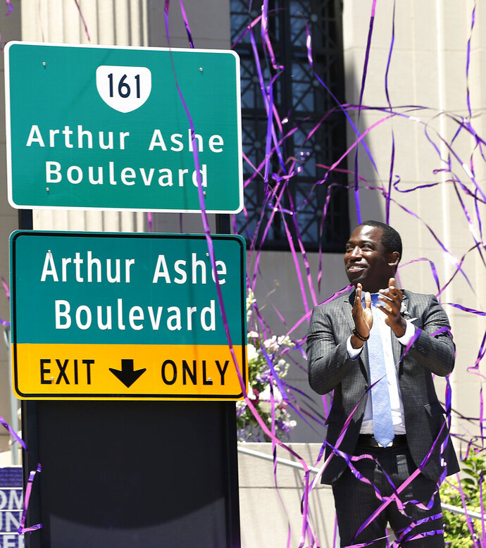 Richmond Mayor Levar Stoney claps after unveiling the he Arthur Ashe Blvd. signs during a renaming the boulevard ceremony at the Virginia Museum of History and Culture in Richmond, Va., Saturday, June 22, 2019. (Alexa Welch Edlund/Richmond Times-Dispatch via AP)