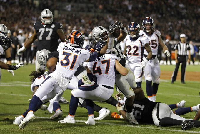 Oakland Raiders running back Josh Jacobs (28) scores a touchdown as Denver Broncos free safety Justin Simmons (31) and inside linebacker Josey Jewell (47) look on during the first half of an NFL football game Monday, Sept. 9, 2019, in Oakland, Calif. (AP Photo/Ben Margot)