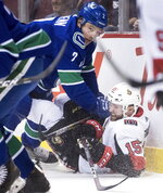 Vancouver Canucks' Luke Schenn, left, checks Ottawa Senators' Zack Smith during the first period of an NHL hockey game Wednesday, March 20, 2019, in Vancouver, British Columbia. (Darryl Dyck/The Canadian Press via AP)