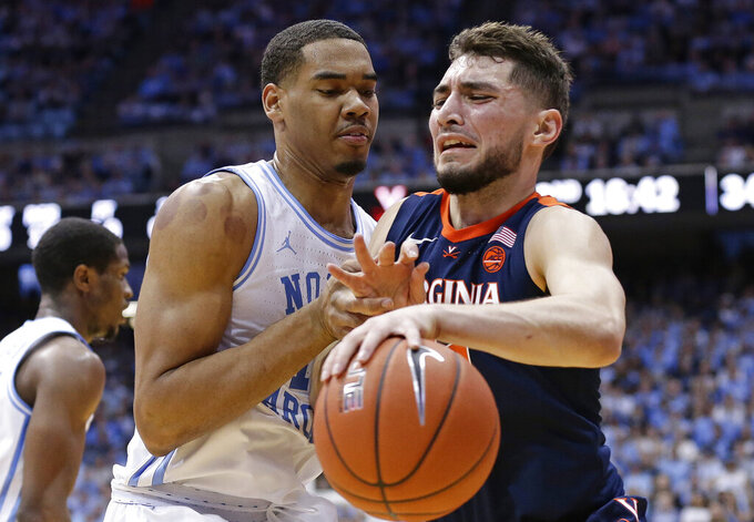 North Carolina's Garrison Brooks, left, guards Virginia's Ty Jerome, right, during the second half of an NCAA college basketball game in Chapel Hill, N.C., Monday, Feb. 11, 2019. Virginia won 69-61. (AP Photo/Gerry Broome)
