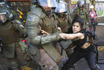 A protester is detained by police during an anti-government protest in Santiago, Chile, Thursday, Oct. 24, 2019. A new round of clashes broke out as demonstrators returned to the streets, dissatisfied with economic concessions announced by the government in a bid to curb a week of deadly violence. (AP Photo/Rodrigo Abd)
