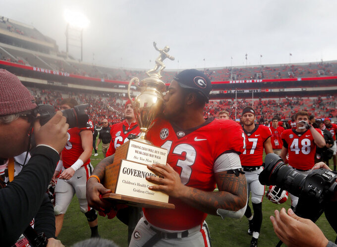 Georgia defensive end Jonathan Ledbetter (13) kisses the Governor's Cup as he leaves the field after defeating Georgia Tech 45-21 in an NCAA college football game Saturday, Nov. 24, 2018, in Athens, Ga. (AP Photo/John Bazemore)