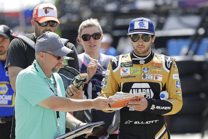 Chase Elliott signs autographs as he walks through the garage area before practice for Saturday's NASCAR All-Star Cup series auto race at Charlotte Motor Speedway in Concord, N.C., Friday, May 17, 2019. (AP Photo/Chuck Burton)