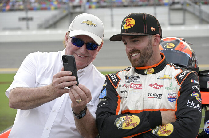 Austin Dillon, right, and car owner Richard Childress share a laugh on pit road before a NASCAR Cup Series auto race at Daytona International Speedway, Saturday, Aug. 28, 2021, in Daytona Beach, Fla. (AP Photo/Phelan M. Ebenhack)