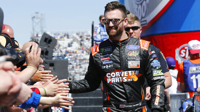 NASCAR Cup Series driver Corey LaJoie (32) greets fans during driver introductions prior to the NASCAR Cup Series auto race at the Martinsville Speedway in Martinsville, Va., Sunday, March 24, 2019. (AP Photo/Steve Helber)