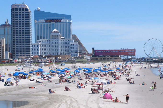 "This July 9, 2018 photo shows the Atlantic City, N.J., beachfront. A report released Wednesday, May 5, 2021, from a state panel recommended rebuilding Atlantic City's Boardwalk, improving the look of its business districts, and embracing the ""blue economy"" of the ocean to help the seaside gambling resort recover from the COVID-19 pandemic. It also suggested money from legalized marijuana sales could help pay for it. (AP Photo/Wayne Parry)"