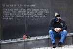 Vietnam Veteran Kitch Kichula, wearing a protective face mask as a precaution against the coronavirus, pays his respects at the at the Vietnam War Memorial, in Philadelphia, on Memorial Day, Monday, May 25, 2020. (AP Photo/Matt Rourke)