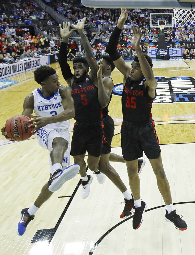 Kentucky's Ashton Hagans (2) passes around Houston's Corey Davis Jr. (5) and Fabian White Jr. (35) during the second half of a men's NCAA tournament college basketball Midwest Regional semifinal game Friday, March 29, 2019, in Kansas City, Mo. (AP Photo/Charlie Riedel)