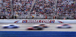 FILE - In this July 16, 2017, file photo, cars steer through Turn 1 as fans watch from nearly half-full stands during the NASCAR Cup Series 301 auto race at New Hampshire Motor Speedway in Loudon, N.H. New Hampshire Motor Speedway will allow fans in the grandstands and suites for the Aug. 2 NASCAR Cup Series race.  Fans will be subject to social distancing requirements and additional health and safety protocols.  (AP Photo/Charles Krupa, File)