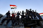 Protesters sit on a concrete wall erected by security forces to close a street leading to the Green Zone government areas, during clashes between Iraqi security forces and anti-government demonstrators in Baghdad, Iraq, Saturday, Nov. 16, 2019. (AP Photo/Hadi Mizban)
