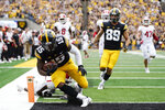 Iowa running back Tyler Goodson (15) scores on a 56-yard touchdown run during the first half of an NCAA college football game against Indiana, Saturday, Sept. 4, 2021, in Iowa City, Iowa. (AP Photo/Charlie Neibergall)