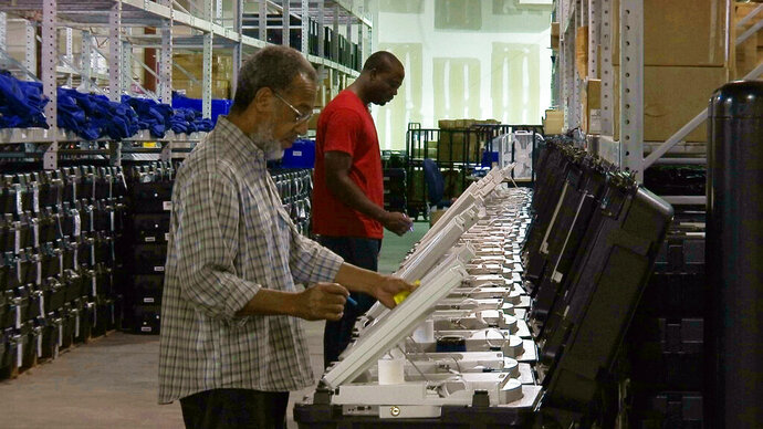 FILE - In this Sept. 22, 2016, file photo, employees of the Fulton County Election Preparation Center in Atlanta test electronic voting machines. A computer security expert says he found that an election server central to a legal battle over the integrity of Georgia elections showed signs of tampering. The server was left exposed to the open internet for at least six months, a problem discovered in August 2016. (AP Photo/Alex Sanz, File)