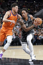 San Antonio Spurs' DeMar DeRozan, right, drives against Phoenix Suns' Devin Booker during the first half of an NBA basketball game, Friday, Jan. 24, 2020, in San Antonio. (AP Photo/Darren Abate)