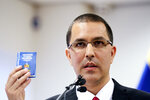 Venezuela's Foreign Minster Jorge Arreaza holds a copy of the constitution as he speaks during a press conference after visiting the International Criminal Court in The Hague, Netherlands, Thursday, Feb. 13, 2020. (AP Photo/Phil Nijhuis)