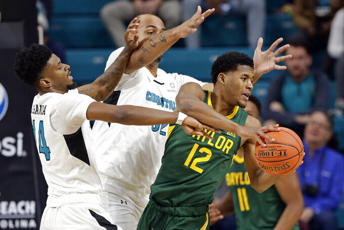 Coastal Carolina guard Malik Legania (14) and center Levi Cook (32) pressure Baylor guard Jared Butler (12) during the first half of an NCAA college basketball game at the Myrtle Beach Invitational in Conway, S.C., Friday, Nov. 22, 2019. (AP Photo/Gerry Broome)