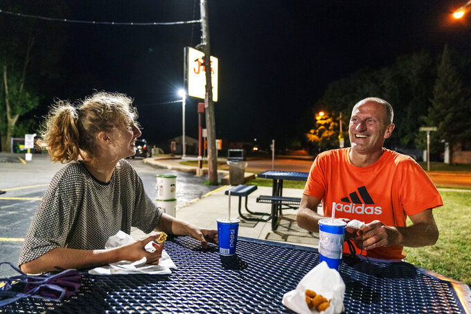 "Scott Rice, right, laughs with his daughter, Cassidy, 20, over burgers at JD's on her last night before she returns to college, Aug. 20, 2020, in Appleton, Wis. Rice concedes that the economy is not just an argument for President Donald Trump, it's also an argument against him. His daughter tells him so. She is studying public health at George Washington University and will cast her first presidential vote for Biden. ""The fact that there was a pandemic and the fact that it had those consequences on the economy should be an eye opener, like, hey, maybe we're not doing this correctly,"" she said. (AP Photo/David Goldman)"