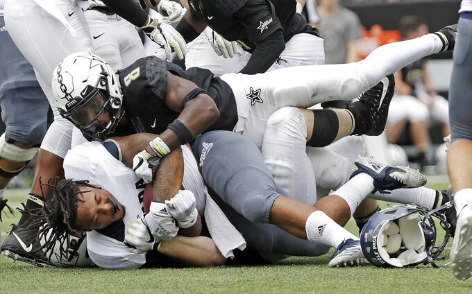 Nevada running back Devonte Lee loses his helmet as he is stopped by Vanderbilt cornerback Joejuan Williams (8) in the second half of an NCAA college football game Saturday, Sept. 8, 2018, in Nashville, Tenn. (AP Photo/Mark Humphrey)