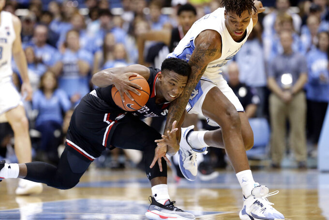 Gardner-Webb guard Jaheam Cornwall, left, and North Carolina forward Armando Bacot (5) struggle for possession of the ball during the first half of an NCAA college basketball game in Chapel Hill, N.C., Friday, Nov. 15, 2019. (AP Photo/Gerry Broome)