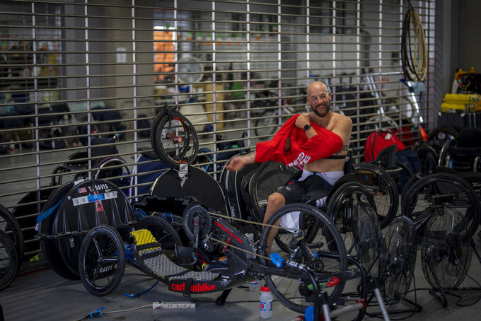Tom Davis, of the U.S., changes clothes after taking part in the Men's H4 Time Trial at the Fuji International Speedway at the Tokyo 2020 Paralympics, Tuesday, Aug. 31, 2021, in Tokyo, Japan. Davis, 44, has emerged as one of the world's fastest hand-cyclists, going into the Tokyo competitions with three world championship silver medals and more marathon victories than he can easily count. (AP Photo/Emilio Morenatti)