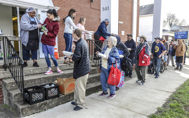 A line forms at the front steps of the Daniel Pitino Shelter as shelter staff serve carry out lunch meals to visitors, Wednesday, March 25, 2020, in Owensboro, Ky. Lunch is normally served in the shelter's dining area but carry out is now the current protocol for the shelter during the coronavirus pandemic. (Greg Eans/The Messenger-Inquirer via AP)