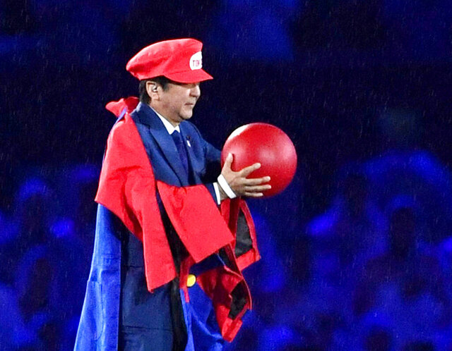 FILE - In this Aug. 21, 2016, file photo, Japanese Prime Minister Shinzo Abe appears as the Nintendo game character Super Mario during the closing ceremony at the 2016 Summer Olympics in Rio de Janeiro, Brazil. Abe was a star of the closing ceremony of the 2016 Rio de Janeiro Olympics, parading before a 70,000 sellout at the Maracana stadium as Nintendo game character Super Mario. It was Abe's humorous invitation to the next Olympics in Tokyo. (Yu Nakajima/Kyodo News via AP, File)