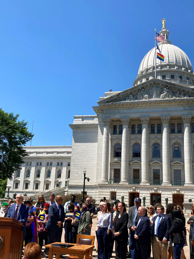 Wisconsin Gov. Tony Evers, at the podium, said he's not ruling out vetoing the entire state budget on Tuesday, June 1, 2021, in Madison, Wis. Evers spoke after a ceremony to raise the rainbow gay pride flag outside the state Capitol in recognition of gay pride month in June in Madison. (AP Photo Scott Bauer)