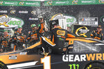 Kurt Busch is showerd in a victory celebration as he gets out of his car after winning a NASCAR Cup Series auto race, Sunday, July, 11, 2021, in Hampton, Ga. (AP Photo/John Amis)