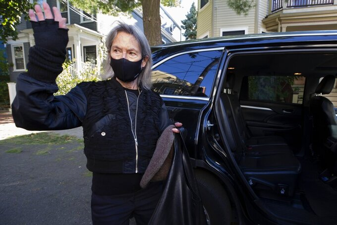 """American poet Louise Gluck waves as she gets in a car, Thursday, Oct. 8, 2020, outside her home in Cambridge, Mass. Gluck, a professor of English at Yale University in New Haven, Conn., won the 2020 Nobel Prize for literature """"for her unmistakable poetic voice that with austere beauty makes individual existence universal."""" (AP Photo/Michael Dwyer)"""