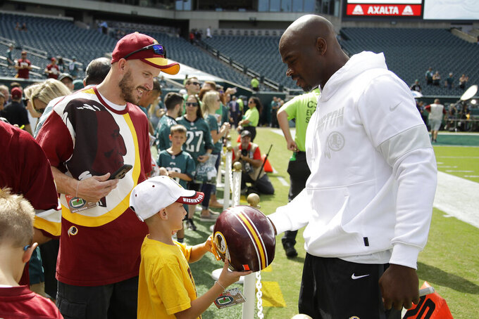 Washington Redskins' Adrian Peterson greets a fan before an NFL football game against the Philadelphia Eagles, Sunday, Sept. 8, 2019, in Philadelphia. (AP Photo/Matt Rourke)