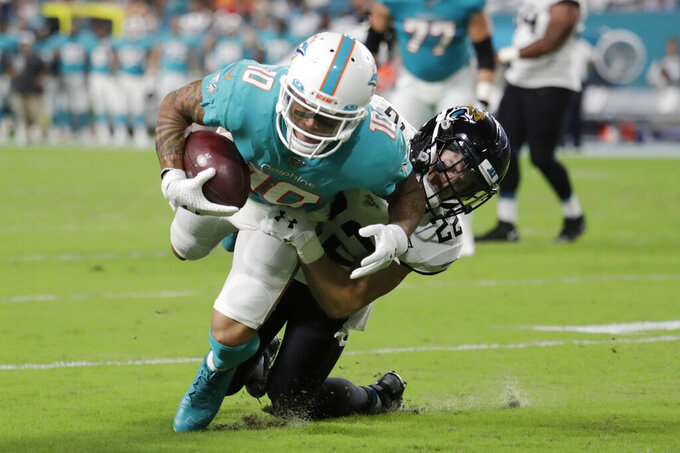 Jacksonville Jaguars safety Cody Davis (22) takes down Miami Dolphins wide receiver Kenny Stills (10) during the first half of an NFL football preseason game Thursday, Aug. 22, 2019, in Miami Gardens, Fla. (AP Photo/Lynne Sladky)