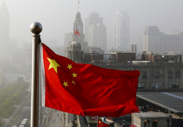 "FILE - In this April 14, 2016 file photo, a Chinese national flag flutters against the office buildings in Shanghai, China. Twitter locked China's U.S. Embassy account because of a tweet in support of China's policies on Muslims and ethnic minorities in the western Xinjiang, The tweet on Jan. 7, 2021 says Uygur women in Xinjiang have been emancipated and are no longer ""baby making machines."" Twitter said it removed the tweet because it violates its policy on dehumanization.  (AP Photo/Andy Wong, File)"