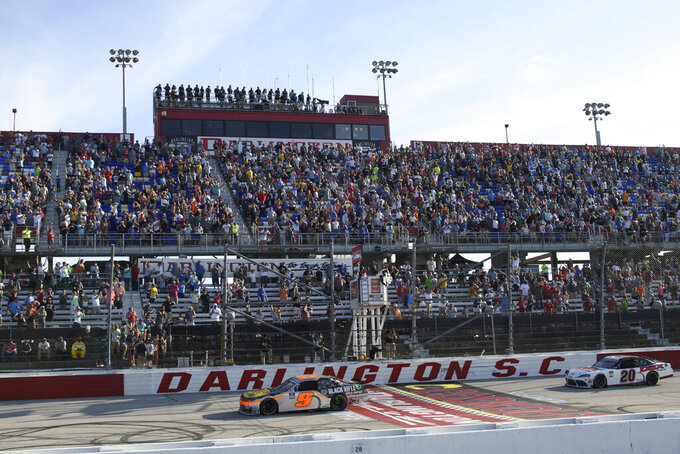 Noah Gragson (9) crosses the finish line to win as Harrison Burton (20) follows in a NASCAR Xfinity Series auto race Saturday, Sept. 4, 2021, in Darlington, S.C. (AP Photo/John Amis)