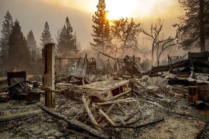 A vintage car rests among debris as the Camp Fire tears through Paradise, Calif., on Thursday, Nov. 8, 2018. Tens of thousands of people fled a fast-moving wildfire Thursday in Northern California, some clutching babies and pets as they abandoned vehicles and struck out on foot ahead of the flames that forced the evacuation of an entire town. (AP Photo/Noah Berger)