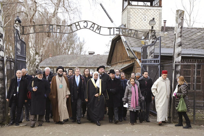 "A delegation of Muslim religious leaders at the gate leading to the former Nazi German death camp of Auschwitz, together with a Jewish group in what organizers called ""the most senior Islamic leadership delegation"