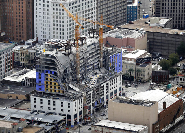 FILE - This Oct. 12, 2019, file photo, shows damage of a partial collapse at the Hard Rock Hotel under construction in New Orleans. New Orleans officials say an unstable hotel building that partially collapsed while under construction last fall will be imploded. Officials say the implosion is expected as early as mid-March. Implosion had been considered, then rejected in the weeks after the Oct. 12 collapse at the planned Hard Rock Hotel. But officials said Friday they've revived the implosion plan. It's deemed safer than having workers on site taking the structure apart. And it means work will be done sooner. Demolition had been expected to last until December. Three workers died in the collapse. The remains of two remain in the wreckage.  (AP Photo/Gerald Herbert, File)