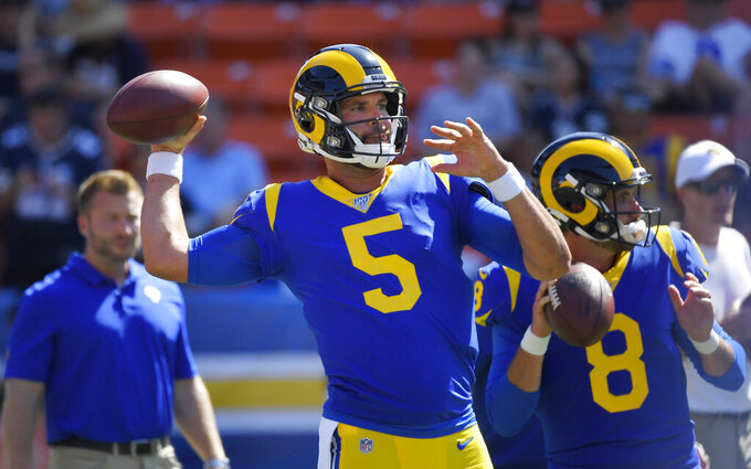 Los Angeles Rams quarterback Blake Bortles, center, throws along with quarterback Brandon Allen, right, as coach Sean McVay watches prior to the team's preseason NFL football game against the Dallas Cowboys on Saturday, Aug. 17, 2019, in Honolulu. (AP Photo/Mark J. Terrill)