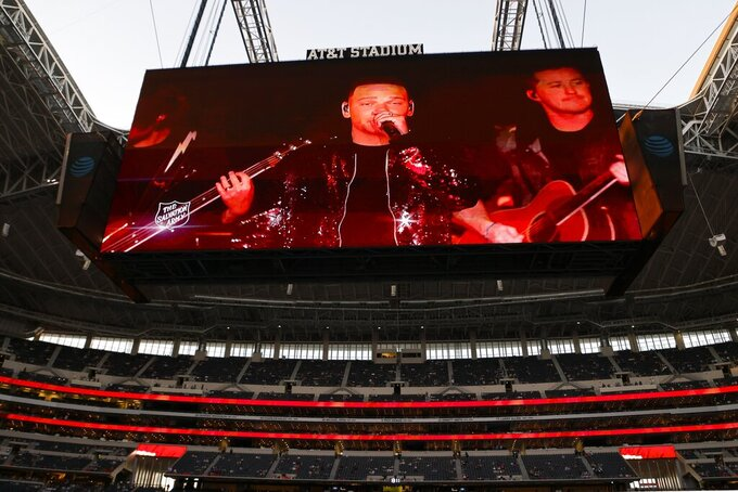 A pre-recorded musical performance by country singer Kane Brown is played on the video board for fans at AT&T Stadium during halftime of an NFL football game between the Washington Football Team and Dallas Cowboys in Arlington, Texas, Thursday, Nov. 26, 2020. (AP Photo/Ron Jenkins)